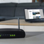 vHome internet connection. A wlan router on desk with notbook in background.